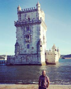O doutorando Jerry Santos Guimarães em Lisboa; ao fundo, a Torre de Belém, às margens do rio Tejo