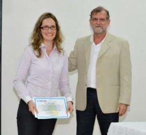 Professora Andrea, coordenadora do Colegiado, recebendo o prêmio pela melhor monografia da área na Bahia